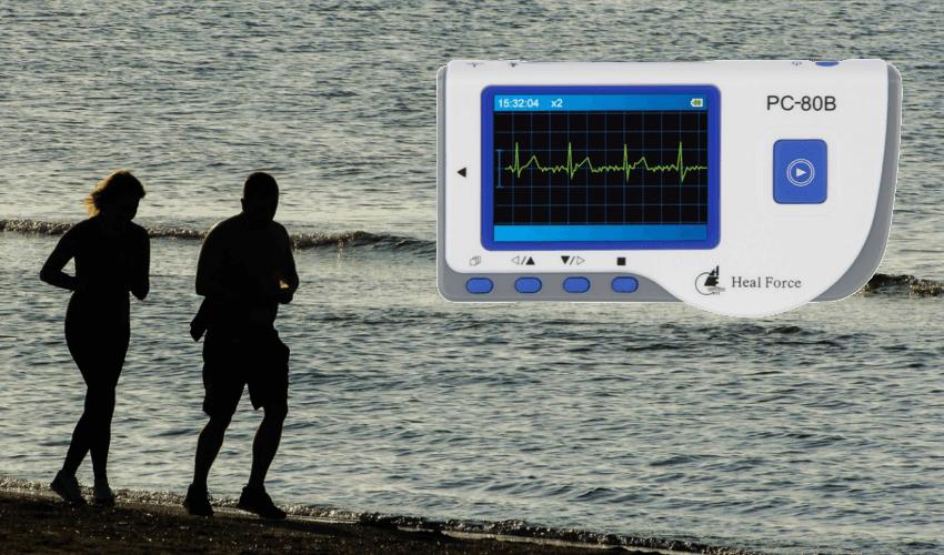 Im Hintergrund zwei Menschen am Strand, im Vordergrund ein EKG Gerät