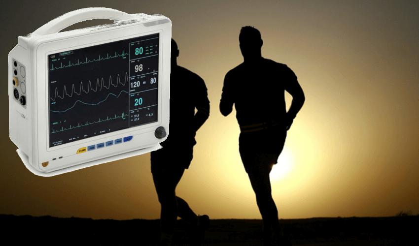 Ein EKG Gerät mit Elektroden, daneben zwei junge Menschen
